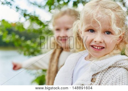 Portrait of two kids as sisters in autumn at park