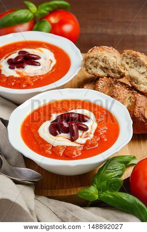 Tomato cream soup with beans on wooden background, selective focus