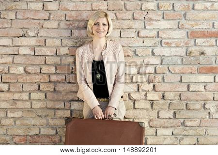 Happy blonde woman holding suitcase leaning against brick wall.