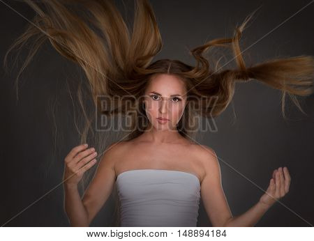 woman with long hair on gray background