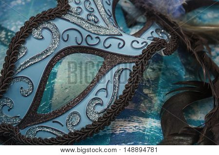 Blue and black female carnival mask on the blue background