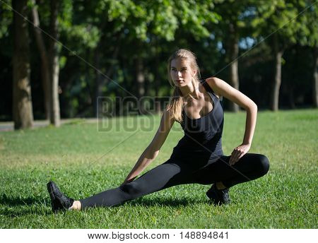 woman doing morning sports exercises in park