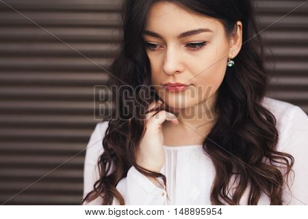 Sad young woman deep in thoughts. Girl thinking and being worried. Hard choice concept.
