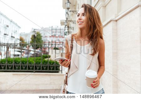 Smiling beautiful girl walking on the street and drinking take away coffee
