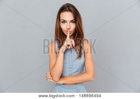 Attractive young woman standing and showing silence sign over grey background