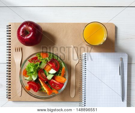 Healthy business lunch in office top view, vegetable salad bowl with wooden cutlery on white wooden desk and notepad with pen. Organic meal, red apple and orange juice. Snack at break time.