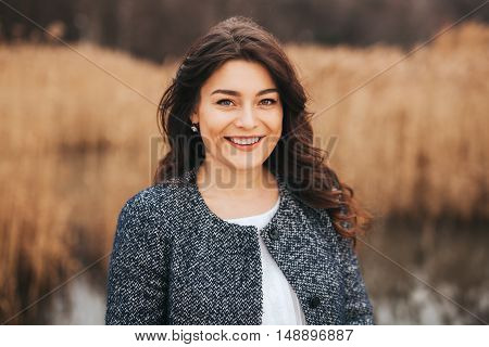 Young woman wearing autumn clothes smiling. Long hair beautiful brunette in grey coat being positive