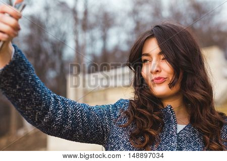 Smiling lady taking selfie and making face grimace on autumn cold day. Young woman holding a smart phone. Toned colors