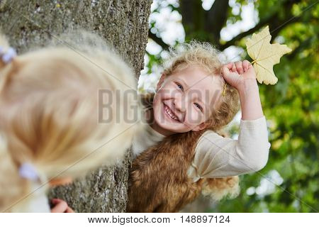 Two kids playing hide and seek at the park in autumn