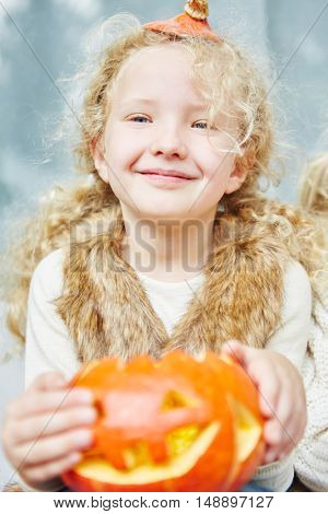 Gril playing with Halloween pumpkin and having fun