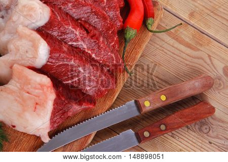 fresh raw beef meat steak's on wooden cut board over wooden table with dill and stainless steel knife