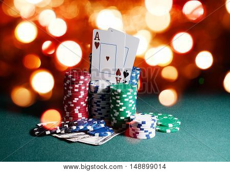 Casino chips and cards, two aces on the playing green table against bright bokeh lights background. Poker game theme backdrop