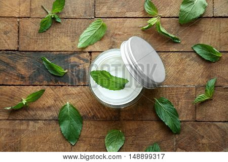 Box with mint cream and fresh leaves on wooden background, top view