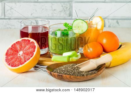 Green, yellow and red smoothies, juices, beverages, drinks variety with fresh fruits and vegetables on a white wooden background.