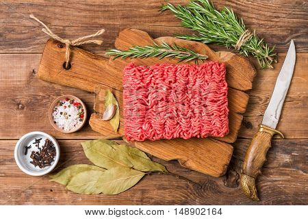 Minced meat on cutting board with seasoning and fresh rosemary on wooden background, top view