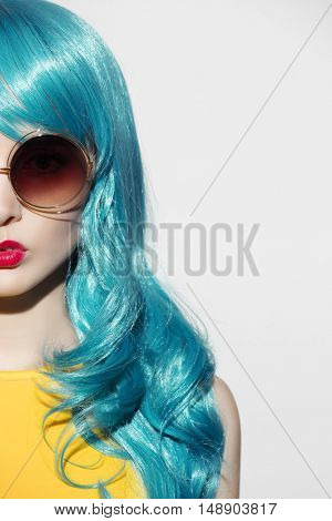 Pop art woman portrait wearing blue curly wig and sunglasses. White background. Space for text.