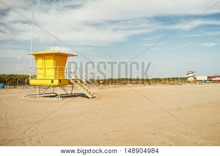 Bright yellow lifeguard post and other distant beach structures on a quiet day with no people around