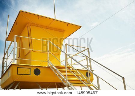 Bright yellow lifeguard post with no lifeguards and windows bolted shut against sky background Commercial image