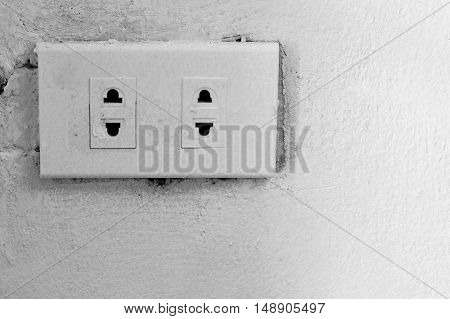 old electrical outlet on wall, black and white tone