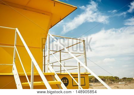 Close up shot of a beautiful yellow lifeguard post against the background of blue sky and some white clouds