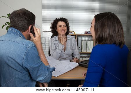Professional business meeting: young couple as customers and an adviser for finance investment or insurance.