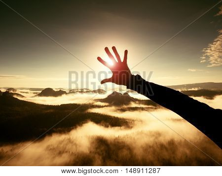 Man hand touch Sun. Misty daybreak in a beautiful hills. Hilly landscape in foggy background the fog is red and orange due to Sun rays. Lens defects. poster