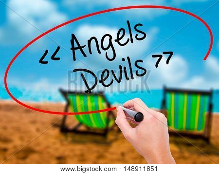 Man Hand Writing Angels - Devils With Black Marker On Visual Screen.