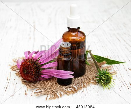 bottle with essence oil with purple echinacea on a wooden background