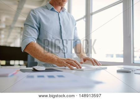 Cropped shot of young man standing at his desk and working on computer. Businessman typing on computer keyboard in modern office.