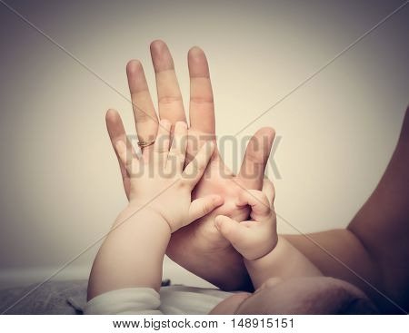 Parenthood. Mother and her little baby touching each other hands. Maternity love concept. Vintage