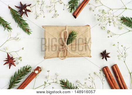 Winter time festive background. Handmade gift box decorated fir tree branch, framed decor little pine boughs, flowers, winter season spices.