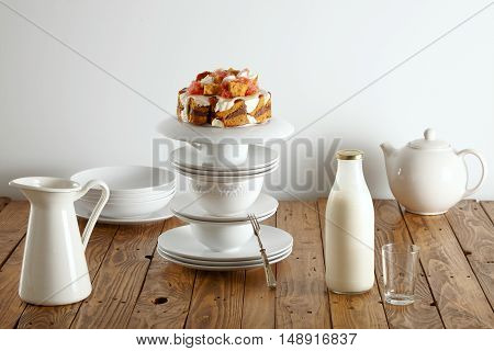 Delicate white tea set, milk bottle and mouthwatering sponge cake with chocolate, cream and grapefruits