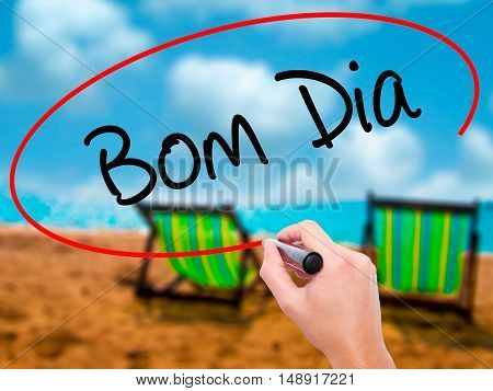"""Man Hand Writing """"bom Dia"""" (in Portuguese - Good Morning)  With Black Marker On Visual Scr"""