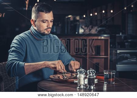 Young handsome man eating at the restaurant