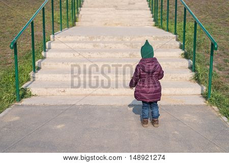 Little girl standing in front of the big staircase. She is standing with her back to the camera. She is wearing a warm coat and a woolen hat. The sunshine is bright.