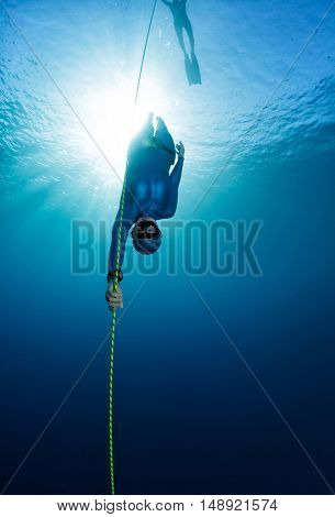 Free diver descending along the rope