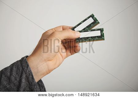 Two RAM chips in a man's hand isolated on white