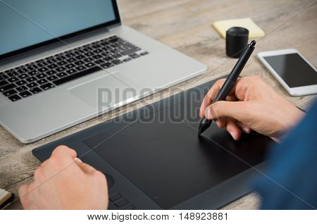 Close up hand of graphic designer drawing on pen tablet at the office. Hand working with graphic tablet on desk with laptop. Close up of man using pen on graphic tablet to complete editing work.