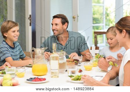 Happy family having lunch together. Family laughing around a good meal in kitchen. Parents and children eating salad for lunch.