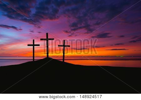 Three crosses on a hill with sunset sky