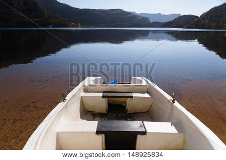 Plastic fishing boat on a still Revsvatnet lake in Norway. Revsvatnet lake situated on the way to touristic attraction, Preikestolen (Pulpit Rock)