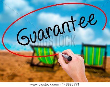 Man Hand Writing Guarantee With Black Marker On Visual Screen.