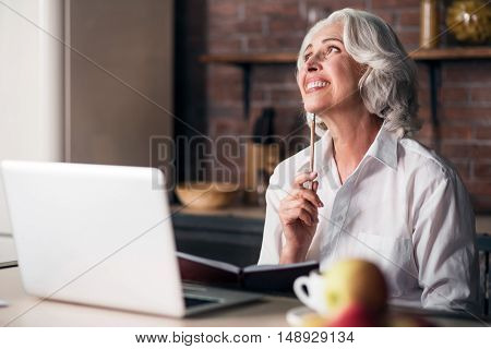 Happy morning. Good-looking grey woman enjoying her breakfast while thinking of writing a letter to her family