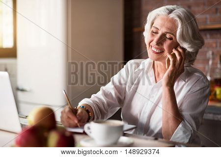 Smiley. Pleasant old lady communicating with her family and friends using telephone and laptop