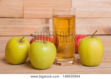 Glass of apple juice and red apples on wooden background