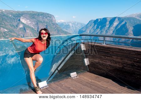 Excited woman tourist at Stegastein Viewpoint in a summer sunny day, Flam, Norway