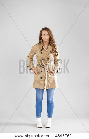 Portrait in full growth of a beautiful young woman in beige autumn coat and blue jeans, isolated on gray background
