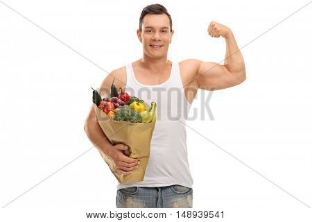 Joyful man holding a shopping bag full of groceries and flexing his bicep isolated on white background