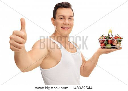Guy holding a small shopping basket full of fruits and vegetables and giving a thumb up isolated on white background
