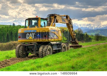 PIENINY MOUNTAINS POLAND - MAY 11 2016: Caterpillar excavator in the area with mountain landscape in background.